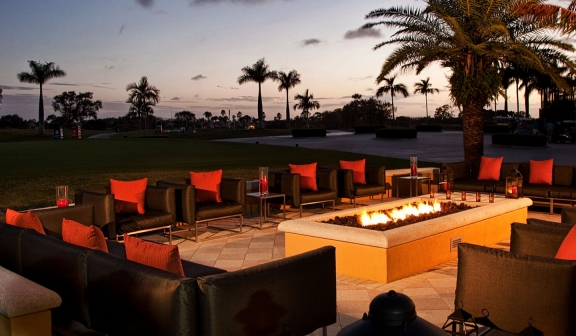 Outdoor patio and fireplace at dusk