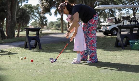 Woman teaching child to play golf