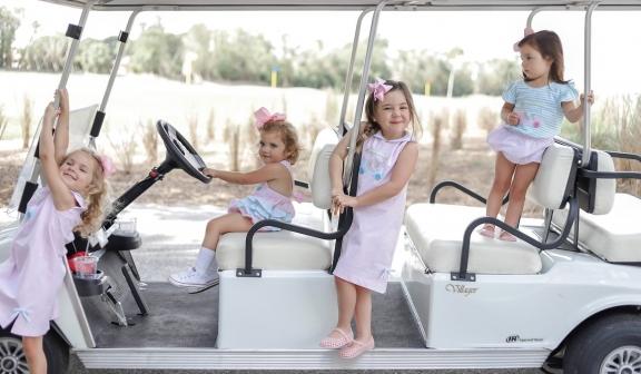 Children posing in golf car