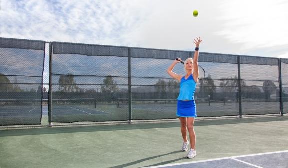 woman serving a tennis ball